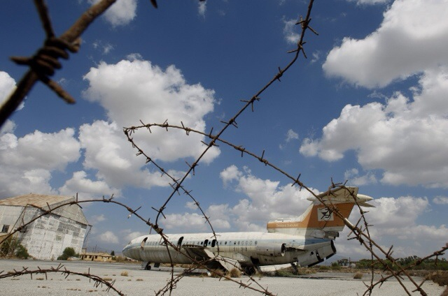 A destroyed Cyprus airways plane behind barbed wire at the war-torn UN buffer zone at the abandoned Nicosia airport during a rare media tour of the defunct facility Tuesday, Sept. 14, 2010. The airport has remained frozen in time after being shut down in 1974 when a coup by supporters of union with Greece prompted Turkey to invade and split the island into a breakaway Turkish Cypriot north and an internationally recognized Greek Cypriot south. The airport was the scene of fierce battles during the invasion and was declared a UN protected area. It now straddles the UN controlled buffer zone separating the rival communities and is home to the UN peacekeeping force's headquarters. It is also the venue for ongoing talks aimed at reunification. But the airport's once bustling main terminal building built in 1968 and hailed as one of the region's best at that time remains under lock and key, ravaged by time and inhabited by pigeons. (AP Photo/Petros Karadjias)
